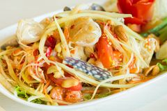 Thai papaya salad with field crab. In white dish on the stone table Royalty Free Stock Photography