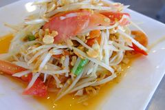 Thai papaya salad or Som Tum on white color dish, Traditional spicy Thai food. Selective focus. stock photography