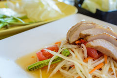 Thai papaya salad on white dish with grilled pork Royalty Free Stock Image