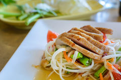 Thai papaya salad on white dish with grilled pork Stock Photography