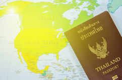 Thai passport lay on north america map. With yellow light royalty free stock images