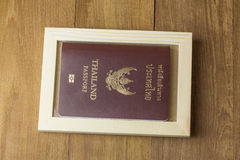 Thai passport and wood frame on wood background. Photo royalty free stock images