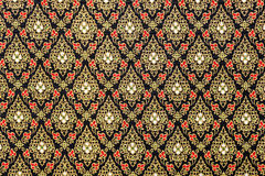 Thai Patterns in Black and Gold  on Silk Fabric. Black and gold Thai style patterns on silk fabric using for background. You might see these patterns on the wall Royalty Free Stock Photo