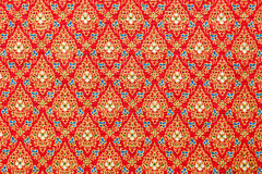 Thai Patterns in Red and Gold  on Silk Fabric. Red and gold Thai style patterns on silk fabric using for background. You might see these patterns on the wall of Royalty Free Stock Images