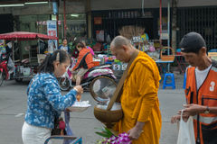 Thai people alms to monks. Bangkok, Thailand - January 30, 2016 : Thai people alms food mony and flower by offering to Thai monks in the morning royalty free stock photo