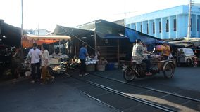 Thai people buy product and food with traffic road and railway with travelers visit at Mae klong Railway Market. SAMUT SONGKHRAM, THAILAND - APRIL 12 : Thai stock video