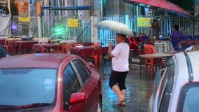 Thai people holding umbrella walking on road while raining stock video
