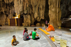 Thai people and monk meditating in a cave Royalty Free Stock Photo