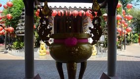 Thai people pray with flower, joss stick and candle at joss stick pot or thurible stock footage