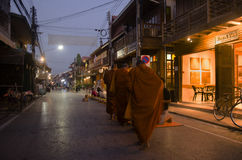 Thai people put food offerings to monks procession walk on the road Stock Images