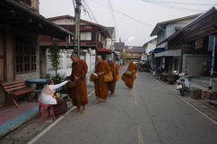 Thai people put food offerings to monks procession walk on the road Stock Photography