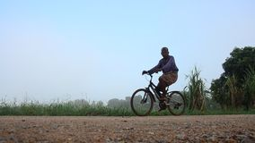 Thai people riding bicycle on Lateritic road at countryside stock video