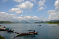 Thai people sail long tail boat serviced for sending and receive. People travel in Cheow Lan Lake at Ratchaprapa or Rajjaprabha Dam Reservoir in Khao Sok Royalty Free Stock Photography