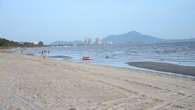 Thai people and traveler travel Bangsaen Beach in Chonburi, Thailand. CHONBURI, THAILAND - AUGUST 10 : Thai people and traveler travel relax and playing wave stock video footage