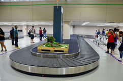 Thai people and traveller wait receive luggage on carousel conve Stock Photos
