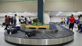 Thai people and traveller wait receive luggage on carousel conveyor stock video
