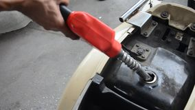Thai people use gas pump nozzle filling gasoline fuel to tank of motorcycle. In oil station at Nonthaburi, Thailand stock video