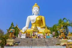 Thai pilgrims worship the big sitting Buddha statue at Wat Phra That Doi Kham Royalty Free Stock Image