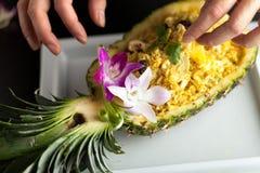 Thai Pineapple Fried Rice. Freshly prepared pineapple fried rice served inside of a pineapple carved like a bowl. Food stylish is arranging garnish royalty free stock photo
