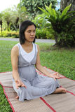 Thai pregnant mom was meditation in the garden. Royalty Free Stock Image
