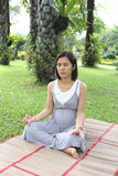 Thai pregnant mom was meditation in the garden. Royalty Free Stock Photo
