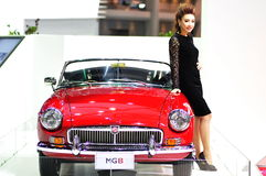 A Thai presenter stands next to a MGB at the 30th  Royalty Free Stock Photo