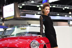A Thai presenter stands next to a MGB at the 30th  Stock Photography