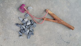 Thai primitive hunting tools. Made from wood and plastic band on the cement floor background Stock Photo