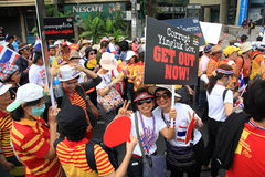 Thai protestors raisng get out Yingluck banner Royalty Free Stock Photo
