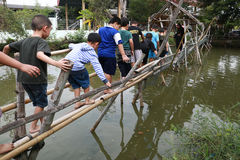 Thai pupills crossing a small canel with bamboo bridge Stock Photography