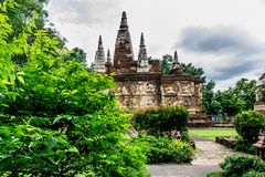 Thai religious achitecture. ChiangMai, Thailand. July, 19-2017: The house of Buddha stands isolately and surrounded by the greeny garden in the temple royalty free stock photo