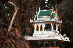 Thai religious green spirit house among trees for worshiping and Stock Photography