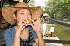 Thai restaurant. Young woman tasted fried chicken royalty free stock photos