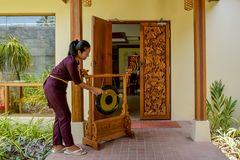 Thai restaurant waitress hitting the gong. Thai restaurant asian waitress in uniform hitting the gong in front of entrance royalty free stock photo