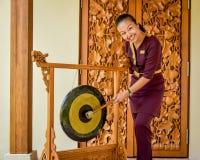 Thai restaurant waitress hitting the gong near entrance. Thai restaurant asian waitress in uniform hitting the gong near entrance in Maldives stock photo