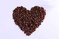 Thai roasted coffee beans in shape of heart on white background Royalty Free Stock Photo