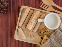Thai rolled wafer and cookie with cup of milk in wooden tray Royalty Free Stock Photography
