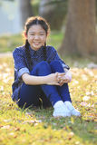 Thai 12s years girl sitting on garden field toothy smiling face Stock Photos