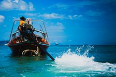 Thai Sailor fisherman on a longtail boat. Drives ship with handmade automobile engine on it. Man in orange hoodie. Sea with liner. And mountains on background stock images