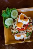 Thai salted egg papaya salad. Fresh prepared asian spicy Som Tam papaya salad served with salted eggs in local restaurant on Koh Lanta island. Traditional thai stock photo