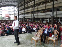 Thai school in Bangkok, Thailand. BANGKOK, THAILAND - DECEMBER 21 : English teacher gives speech while students sit outside for assembly at Seekan school Stock Image