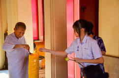 Thai schoolgirl helping a nun lighting giant c Stock Photos
