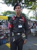 Thai security guard, Bangkok. BANGKOK, THAILAND - JANUARY 20 : Thai old police man stands on guard in Chatuchak market. January 20, 2006 in Bangkok Royalty Free Stock Photography