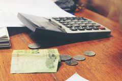 Thai sedel för räknemaskin och för pengar med vitt anteckningsbokpapper, penna på hemmastatt kontor för trätabell Begreppet av de Arkivfoton