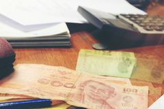 Thai sedel för räknemaskin och för pengar med vitt anteckningsbokpapper, penna på hemmastatt kontor för trätabell Begreppet av de Royaltyfria Bilder