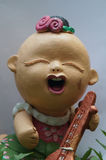 Thai smile doll. Asian design earthenware.The doll made in Thailand.It`s Thai design and style. The doll wearing Thai dress play Thai instruments.Put it in Royalty Free Stock Images