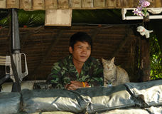 Thai Soldier and Cat Guarding Together at Roadbloc. Thai Soldier and Cat at Doi Tung Road block Thailand Royalty Free Stock Image