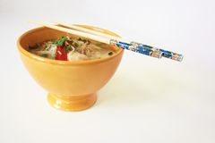 Thai soup. Traditionnal spicy asian soup in a yellow bowl with chopsticks Royalty Free Stock Images