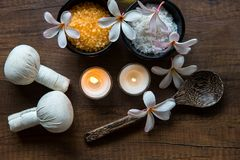 Thai spa composition treatments aroma therapy with candles and Plumeria flowers. On wooden table close up. Healthy Concept stock photography