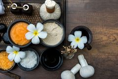 Thai spa composition treatments aroma therapy with candles and Plumeria flowers on wooden table close up. Royalty Free Stock Photography